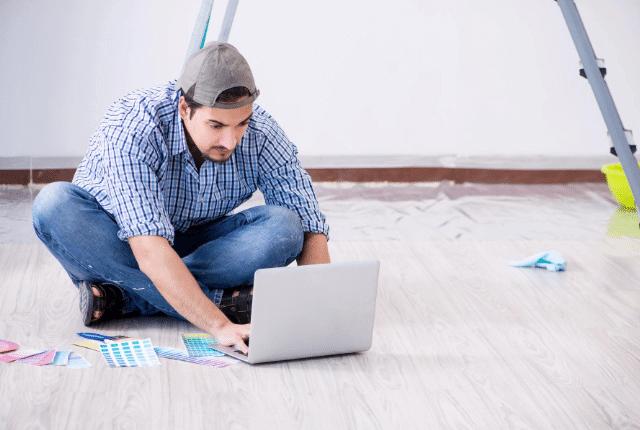 בחור בדירה חדשה על הרצפה עם מחשב נייד