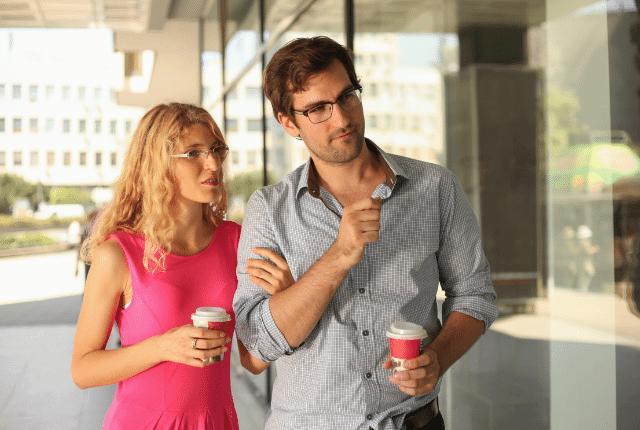 זוג מהלך ברחוב עם קפה ושמח