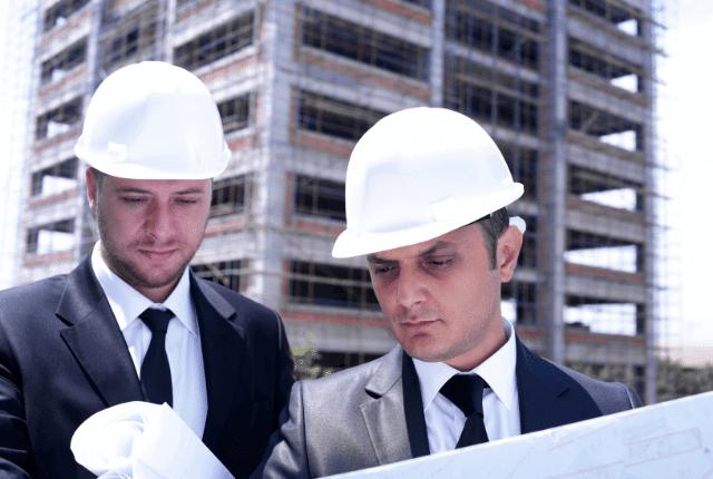 קבלני בנייה רואים את התוכניות באתר הבנייה